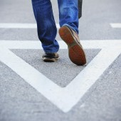 Close up of Man walking in the middle of the road. Alone. Painted triangle. Close up on feet / shoes.