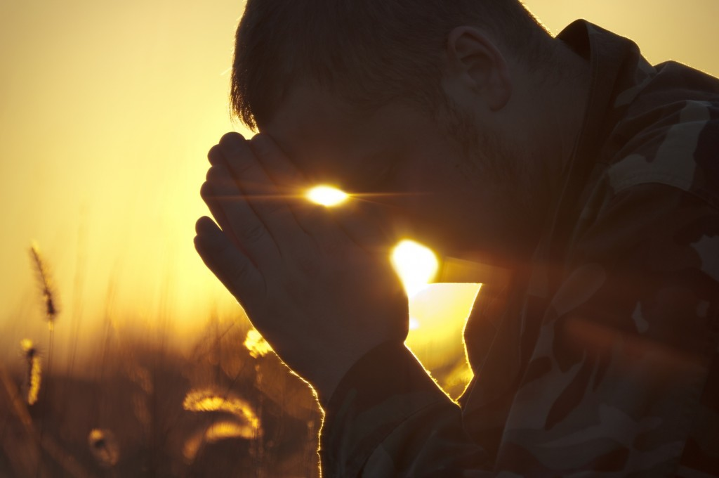 Man Praying Outside in Field at Sunset