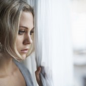 young blonde woman looking out of her window sadly