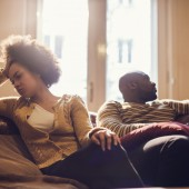 Young African American couple sitting at home angry at each other.