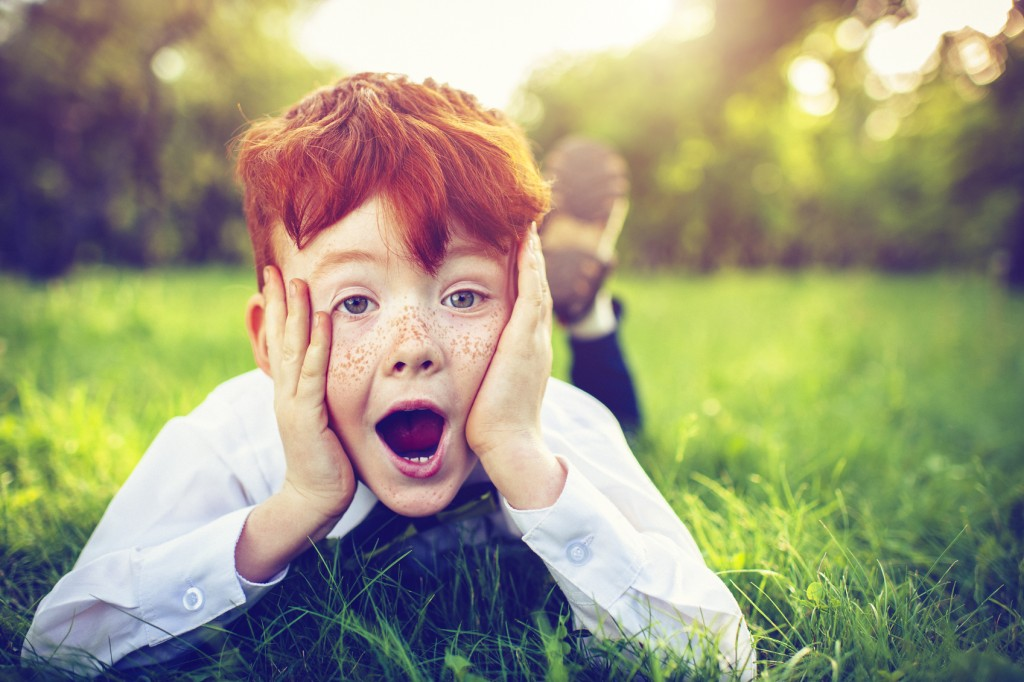 Surprised child with red hair and freckles in park in summer
