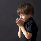 Little boy praying, child praying, isolated black background
