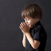 Little boy praying, child praying, isolated black background