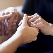 Cropped shot of a person holding an elderly woman's hands
