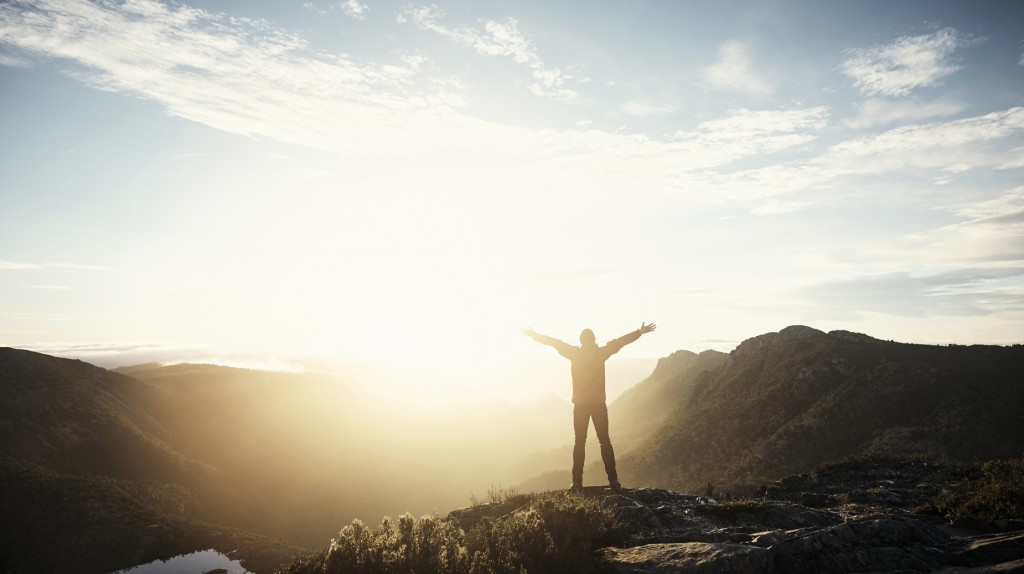 Shot of a young hiker standing with his arms outstretched on top of a mountain