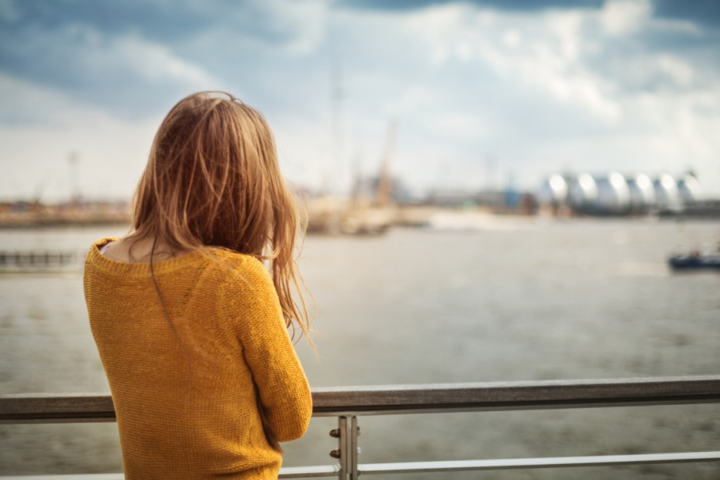 A woman, with her back to the camera, at the harbor of Hamburg.