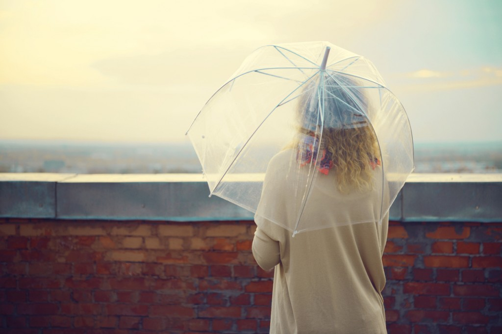 young woman standing on a roof under a transparent umbrella and looking at the horizon
