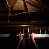 Woman's hands playing on the keyboard of the piano in night closeup