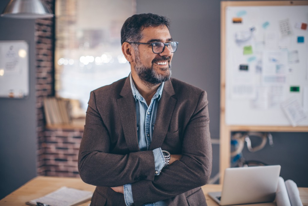 Mature business man working in modern office. Standing in front office and looking away witn his arms crossed. Wearing casual clothes and glasses.