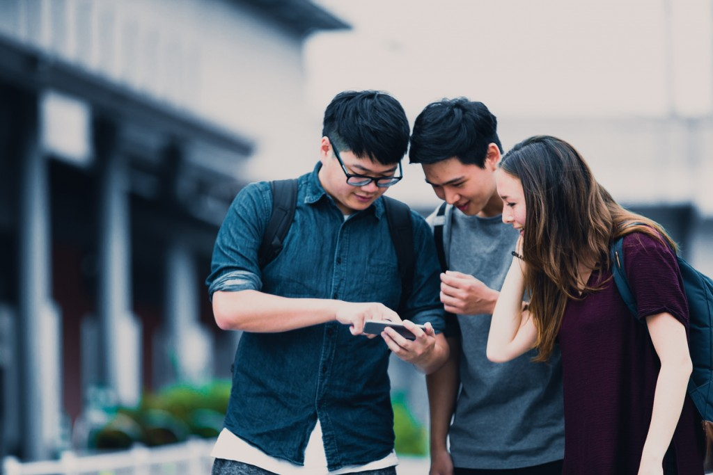 Group of International Students exploring Social Media feed on Smartphone.