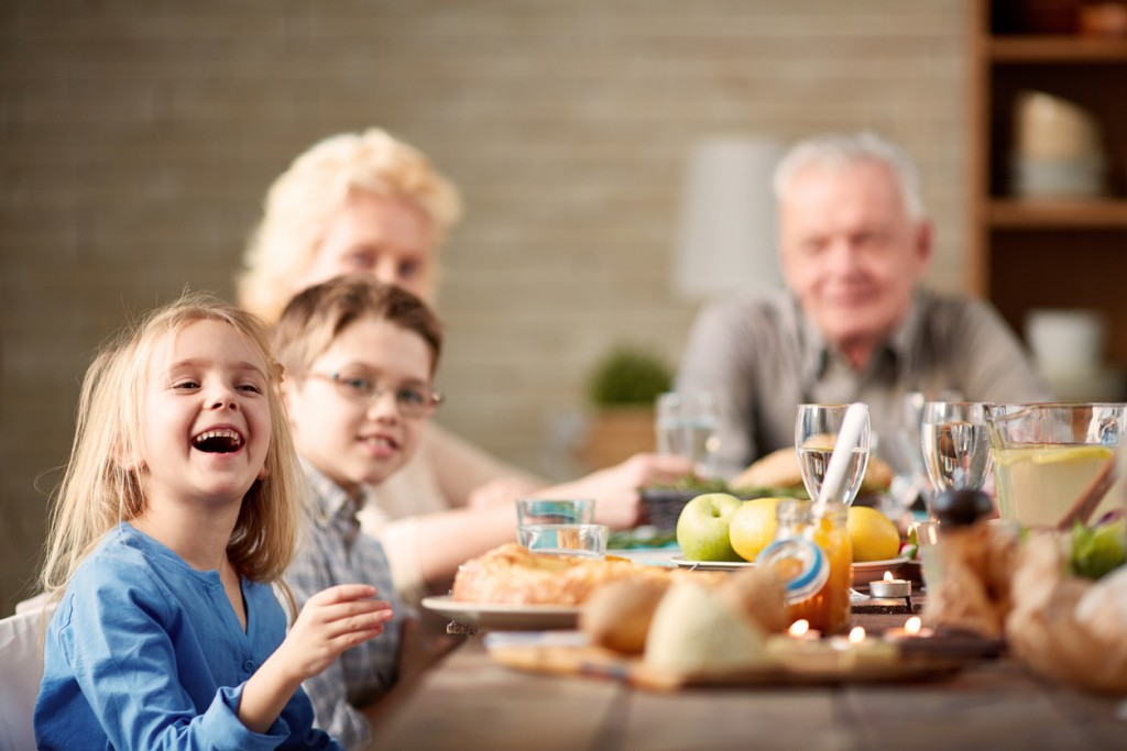 Little girl laughing at multi-generation family dinner