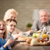 Little girl laughing at multi-generation family dinner
