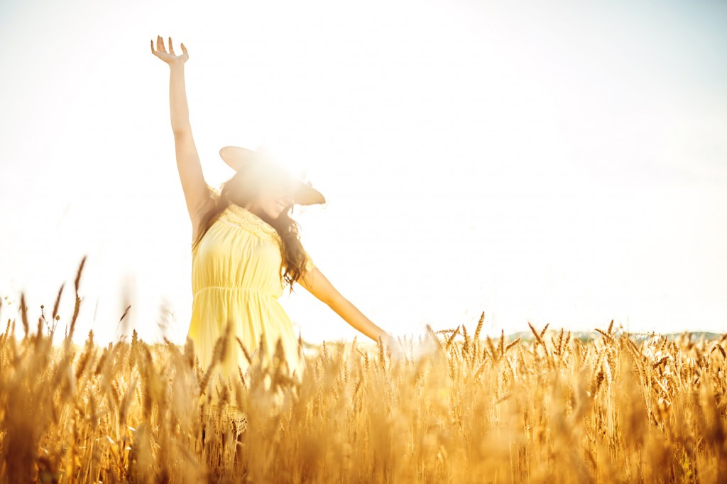 young woman enjoying on a wheat field on sunny summer day