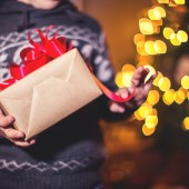 Closeup of child holding holiday gifts,by the Christmas tree