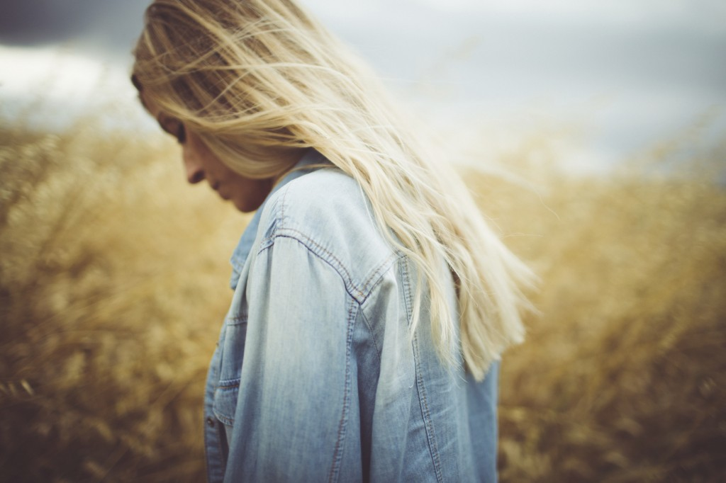 Photo of a young woman standing in the middle of a wheat field, walking away from her