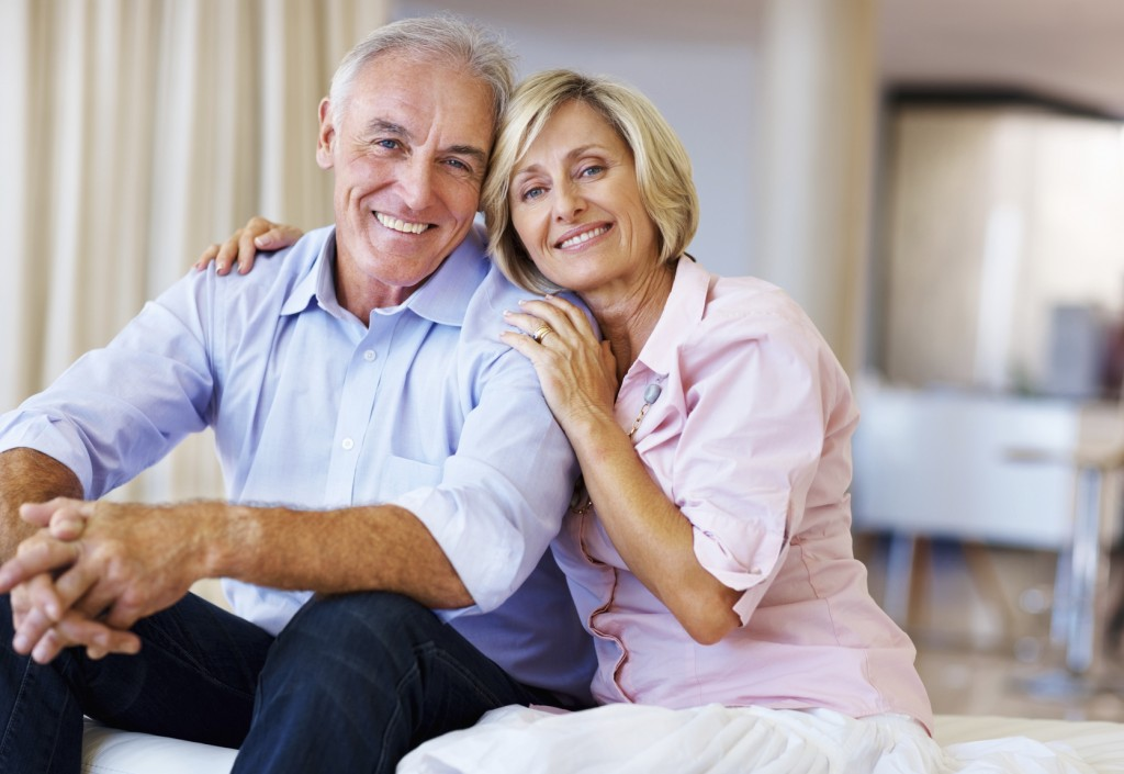 Portrait of happy senior couple sitting and smiling together at home