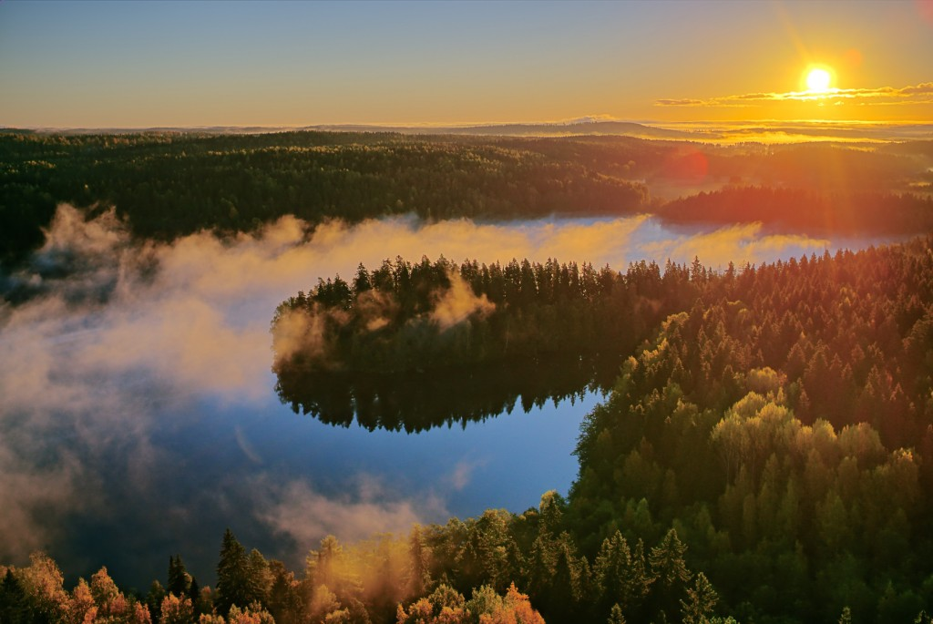 Foggy aerial view of the Aulanko nature reserve park in Finland. The sun hits the fog above the lake in the early morning. HDR image.
