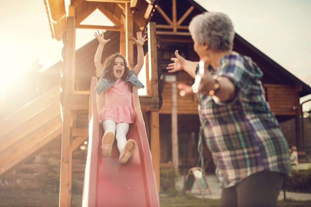 Little girl sliding and having fun outdoors with her grandmother.