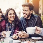 Group of smiling young people in a coffee shop.