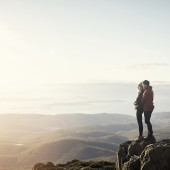 Shot of a young couple looking down at the view from the top of a mountain
