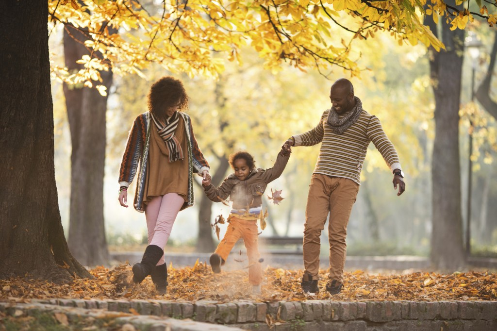 African American family holding hands and having fun while walking in autumn park.
