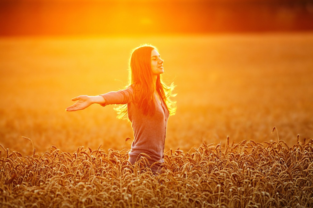 Young woman enjoying nature and sunlight in straw field.