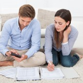 Full length of couple calculating budget in living room at home