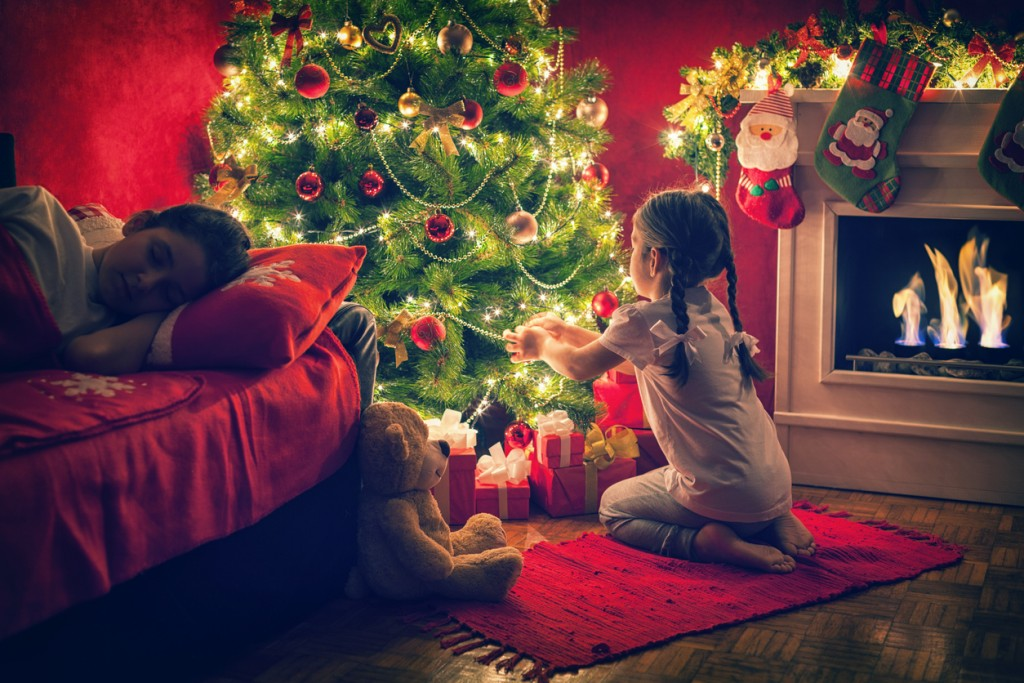 beautiful little girl sitting and playing with her toy teddy bear in front of a Christmas tree, while her sister sleeps