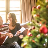 couple reading a book on christmas on the living room