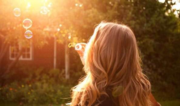 Woman enjoying the sun outdoors in sunset, blowing soap bubbles.