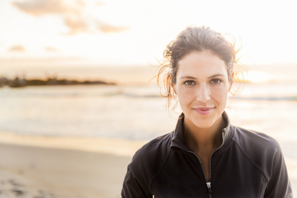 A photo of fit young woman with confident look on her face. Portrait of happy female athlete is at beach. She is wearing sportswear during sunset.