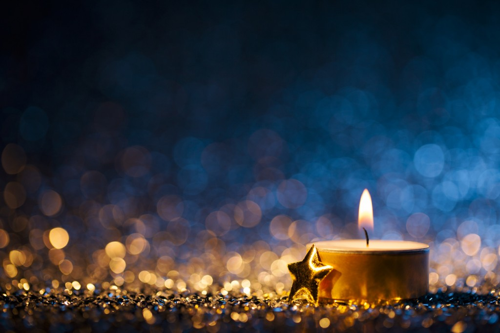 Lighted candle on defocused blue background - Christmas Tea Light
