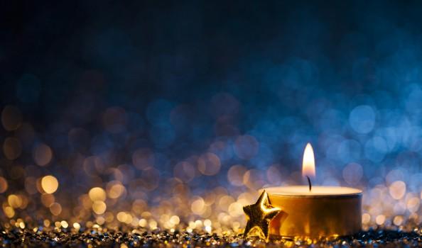 Lighted candle on defocused blue background - Christmas Tea Light