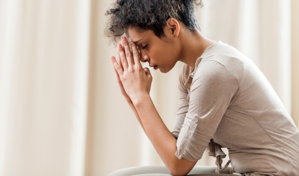 Young African American woman at home praying with her eyes closed.