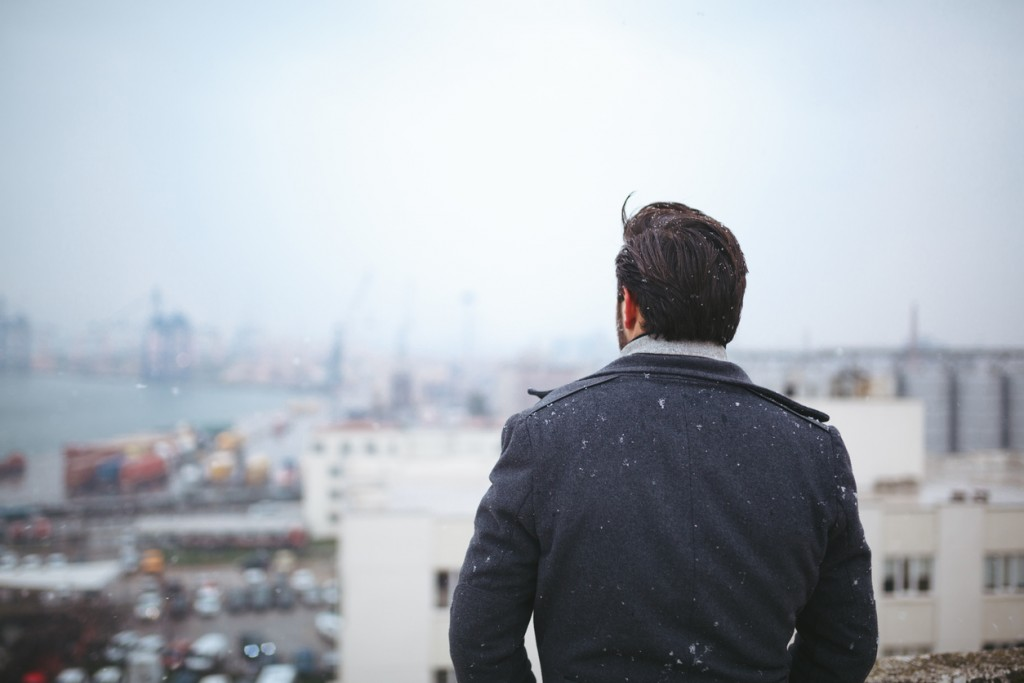 Young adult man standing looking away on a cold day