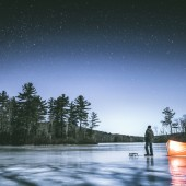 Man standing on the frozen lake in Connecticut's dark and wild north west corner of the state, next to his tent looking up observing stars on cold full moon winter night.