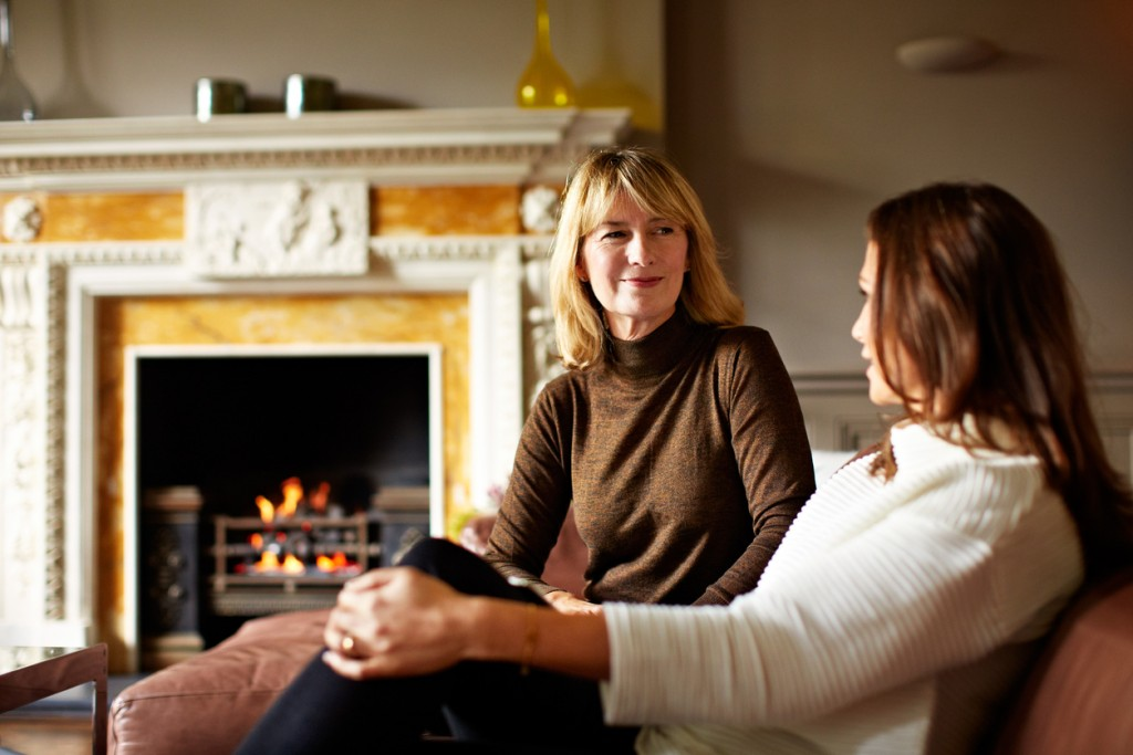 Shot of a woman talking with her mother on the living room sofa