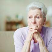 Elderly woman keeping hands by her lips