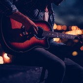 Close up of a teenage man playing an acoustic guitar on a rooftop of a building at night with citylight in the background