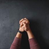 Praying hands on black desk.