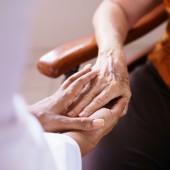 Doctor Vising Senior Woman In Old People Home