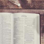 Bible with tablet and coffee in a wooded table..