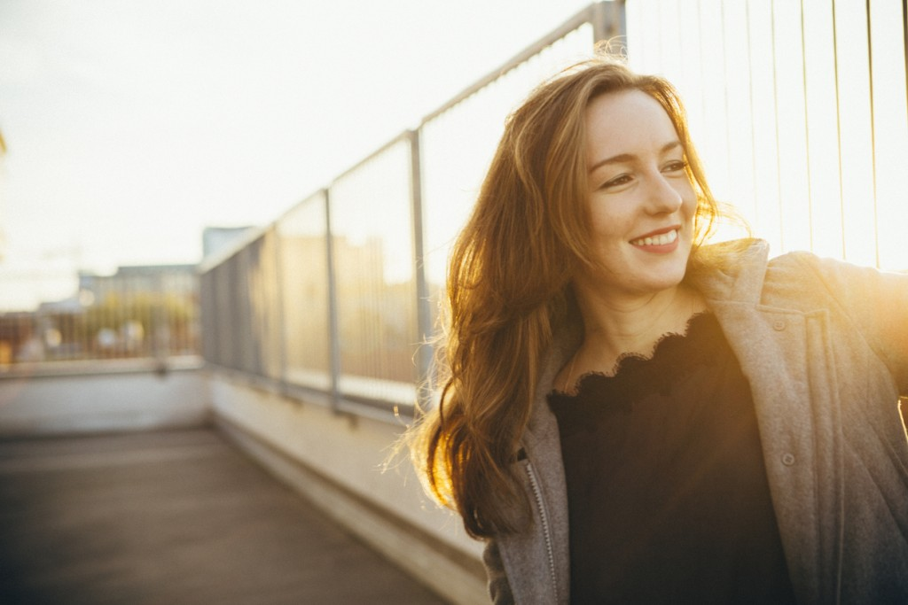 laughing young woman portrait in urban scene with backlit