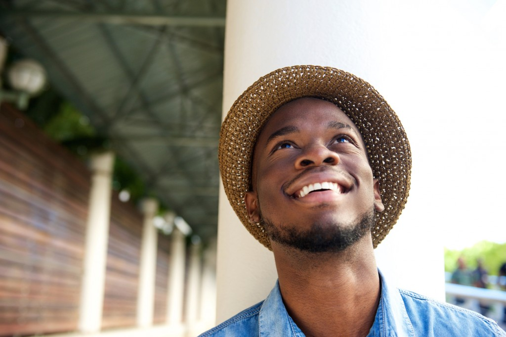 Close up portrait of a happy young man smiling and looking up