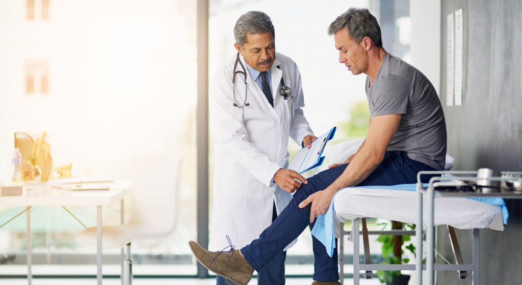 Shot of a mature doctor examining his patient who is concerned about his knee