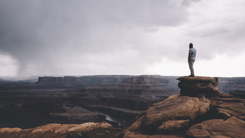 Man standing on the top of the rock overlooking Canyonlands enjoying the vast landscape view.