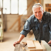 Close up of a smiling mature carpenter at work
