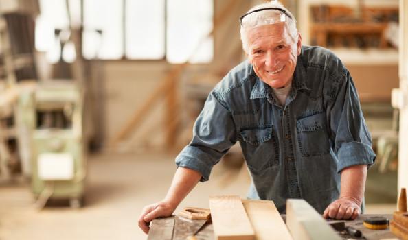 Close up of a smiling mature carpenter at work
