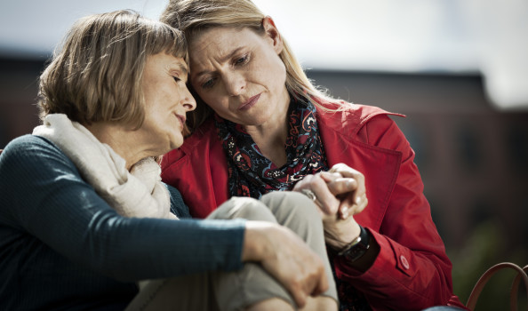 Mature woman and her adult daughter sitting close to each other with sad expression on their faces. Younger woman is holding her mother's hand.