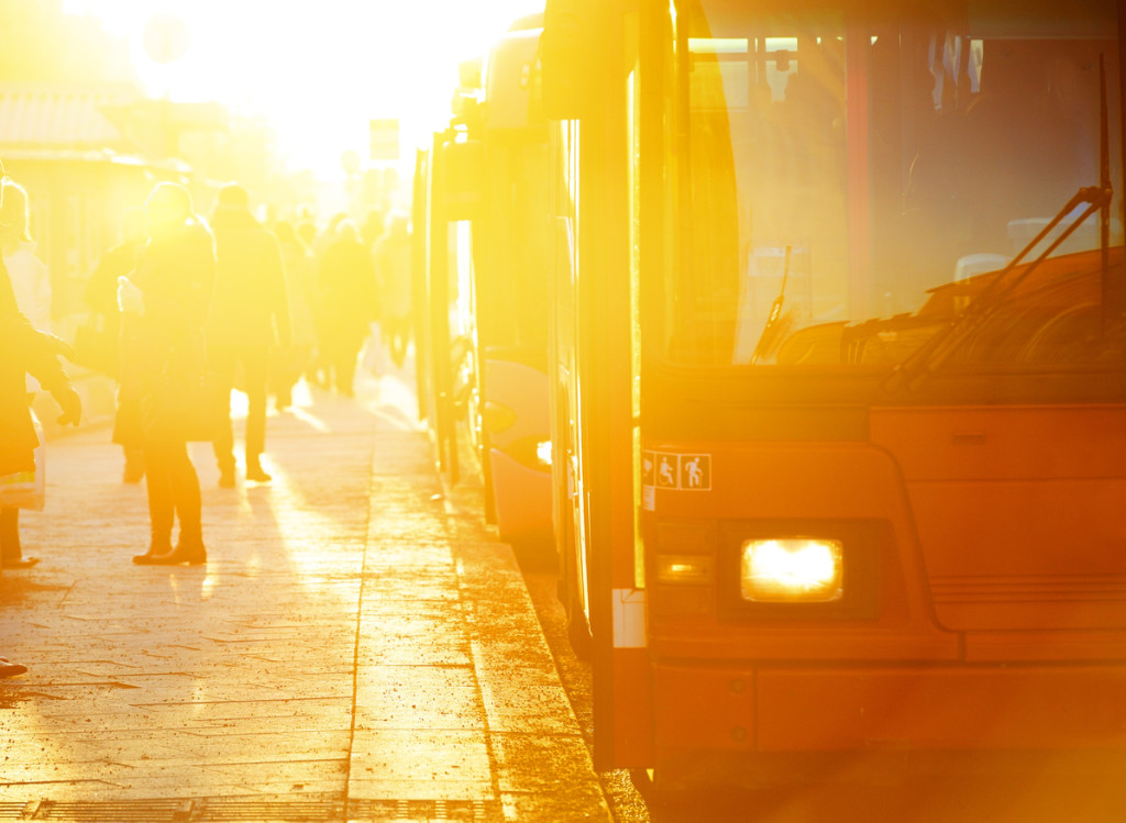 People and bus station bus stop. Commuter bus ready to go. Shot straight into sun, light effect not from post processing.
